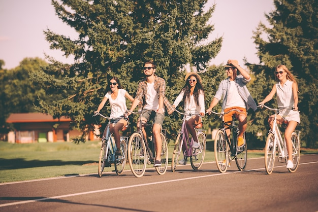 Journée parfaite pour faire du vélo. groupe de jeunes faisant du vélo le long d'une route et ayant l'air heureux