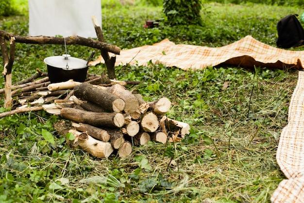 Journée pique-nique avec tente de camping verte touristique et pot sur le feu dans un camping en plein air dans les bois