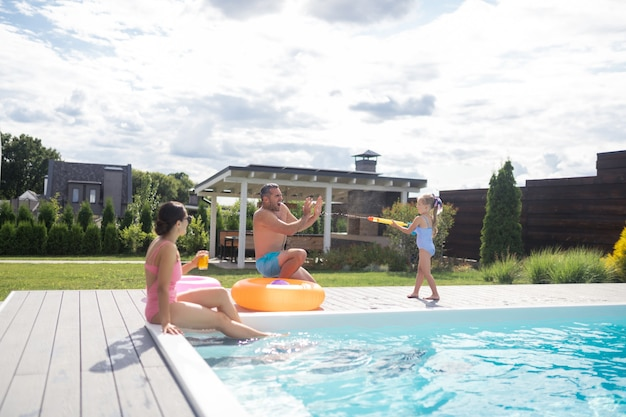 Journée près de la piscine. fille mignonne gaie éclaboussant l'eau sur le père tout en passant la journée près de la piscine