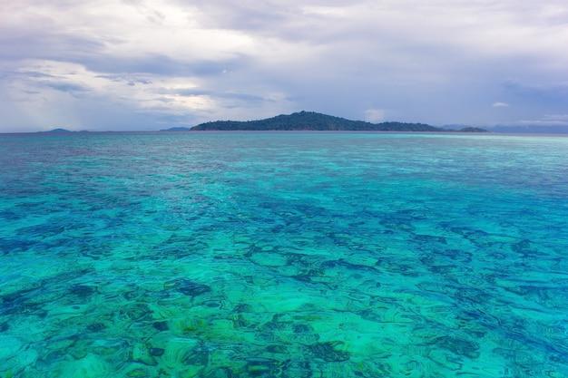 Journée principalement nuageuse avec un océan vert bleu où l'on peut voir des coraux sur le sol marin et la montagne