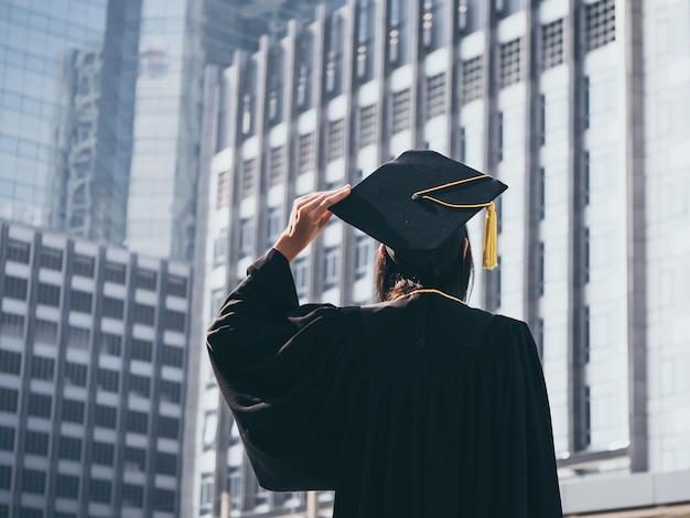 Journée de remise des diplômes, vue arrière de la femme asiatique avec cap de graduation et diplôme de tenue de robe