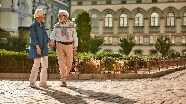 Journée romantique beau et heureux couple de personnes âgées se tenant la main et parlant de quelque chose tout en