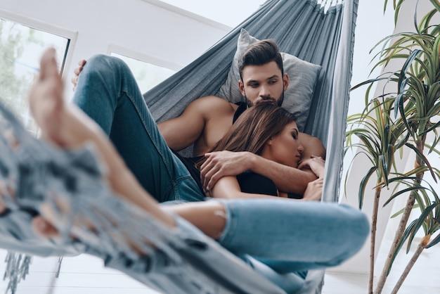 Journée sans soucis ensemble. beau jeune couple embrassant tout en se reposant dans le hamac à l'intérieur