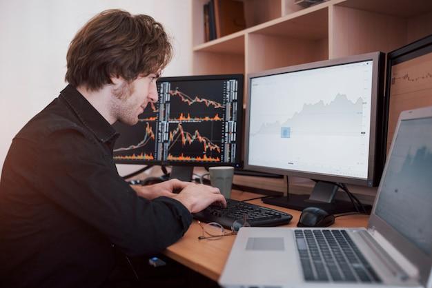 Journée stressante au bureau. jeune homme d'affaires, main dans la main sur son visage, assis au bureau dans le bureau créatif. stock exchange trading forex finance concept graphique