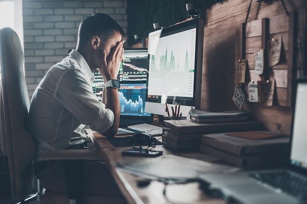 Journée stressante au bureau. jeune homme d'affaires tenant la main sur son visage alors qu'il était assis au bureau dans un bureau créatif