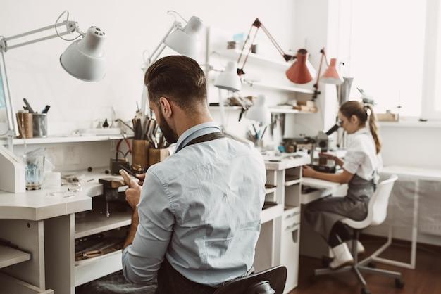Journée de travail en atelier. l'équipe de bijoutiers travaille ensemble dans un atelier de fabrication de bijoux. entreprise