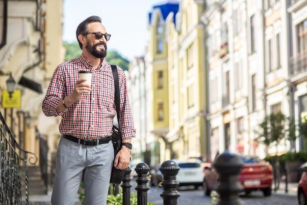 Des journées agréables. joyeux bel homme d'affaires marchant le long de la rue tout en buvant du café avec plaisir