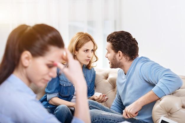 Jours ouvrables habituels. belle belle psychologue professionnelle assise dans son bureau et écoutant la querelle de ses clients tout en ayant une séance psychologique avec eux
