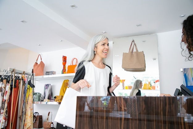 Joyeuse acheteuse tenant des sacs en papier et souriant au caissier ou au vendeur dans un magasin de mode. femme prenant l'achat et quittant la boutique. coup moyen. concept d'achat
