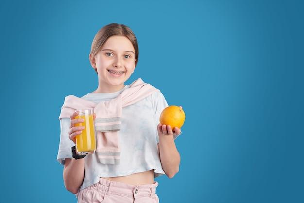 Joyeuse adolescente avec verre de jus et orange fraîche debout devant la caméra tout en allant avoir les fruits et boire en isolement