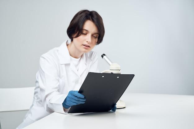 Joyeuse assistante de laboratoire dans des expériences scientifiques professionnelles au microscope à blouse blanche