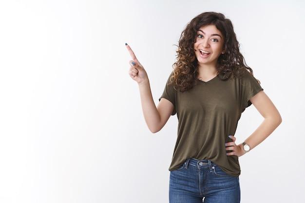 Joyeuse bavarde charmante jeune fille arménienne aux cheveux bouclés debout optimiste excité pointant le coin supérieur gauche promouvant les services l'air brillant optimiste debout joyeusement fond blanc