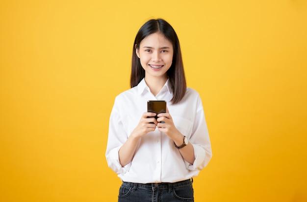 Joyeuse belle femme asiatique tenant un smartphone et en tapant un message