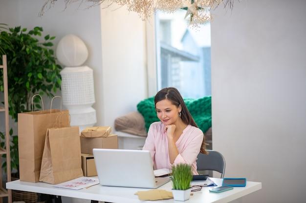 Joyeuse belle femme assise devant l'écran de l'ordinateur portable tout en vendant différents cadeaux en ligne