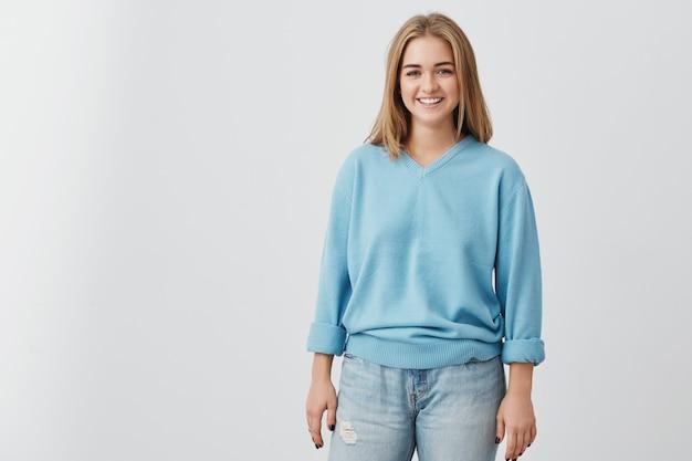 Joyeuse belle femme aux cheveux blonds raides ayant des yeux charmants sombres et un sourire engageant posant au studio. fille très souriante portant un pull bleu et un jean.