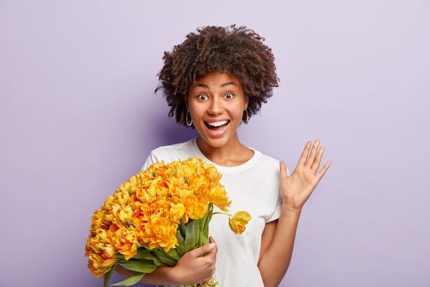 Joyeuse belle femme ravie tient des tulipes jaunes aromatiques, des vagues avec la paume, salue des amis, étant reconnaissant pour les félicitations, a une coupe de cheveux afro, porte un t-shirt blanc, des modèles sur un mur violet