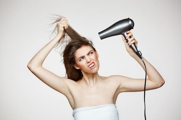 Joyeuse belle femme en serviette souriant rire en chantant avec sèche-cheveux faisant la grimace. spa de beauté et cosmétologie.