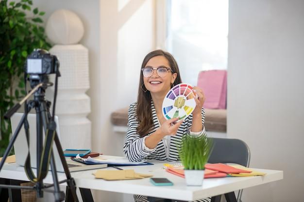 Joyeuse belle femme souriante tout en parlant à la caméra sur la conception