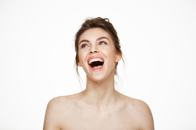 Joyeuse belle fille nue se réjouissant souriant en riant sur fond blanc. traitement facial. beauté et santé.