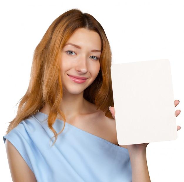 Joyeuse belle jeune femme montrant une feuille de papier vierge avec espace de copie
