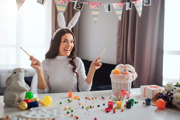 Joyeuse belle jeune femme se prépare pour pâques seule. elle est assise à table dans la chambre et pose devant la caméra. le modèle tient les pinceaux dans les mains. bonbons peinture et décoration sur table.
