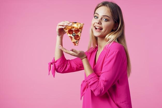 Joyeuse blonde avec une pizza dans ses mains fond rose de collation de malbouffe