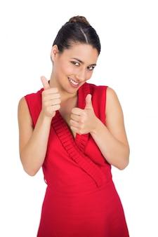 Joyeuse brune sexy en robe rouge pouce en l'air