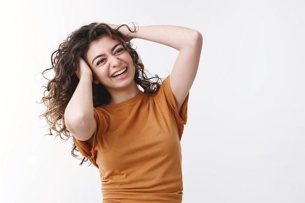 Joyeuse charismatique souriante chanceuse jeune fille caucasienne cheveux noirs bouclés secouant la tête jouant à la coiffure riant joyeusement faisant la promotion de produits de soins capillaires se sentir chanceux bonne humeur journée parfaite s'amuser