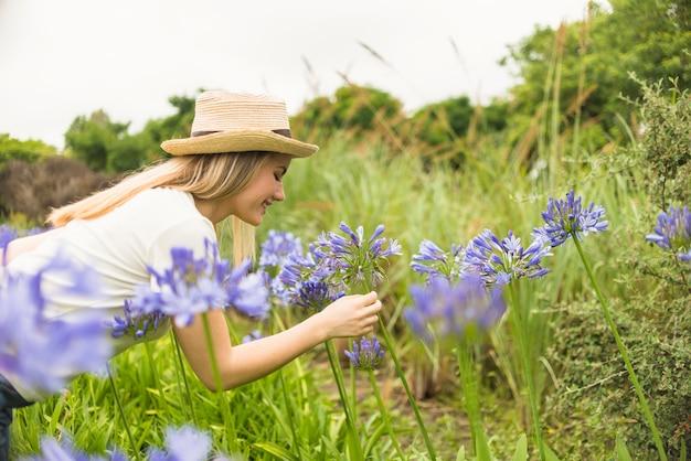 Joyeuse dame au chapeau près des fleurs bleues dans le parc