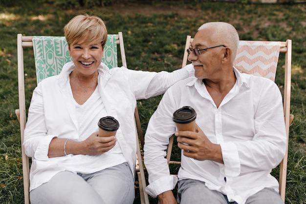 Joyeuse dame aux cheveux courts blonds en chemisier blanc en riant, tenant une tasse de thé et posant avec un vieil homme à lunettes en plein air.