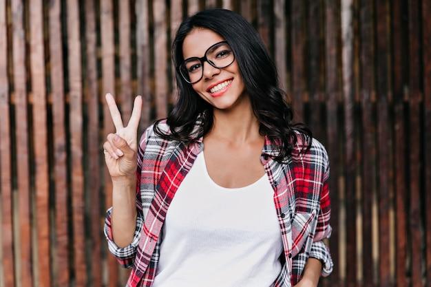 Joyeuse dame aux cheveux ondulés noirs posant avec signe de paix. fille intéressée dans des vêtements décontractés à la mode se détendre le matin de printemps.