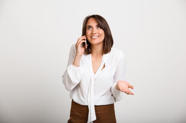 Joyeuse dame de bureau parler au téléphone