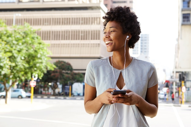 Joyeuse dame dans la rue en écoutant de la musique