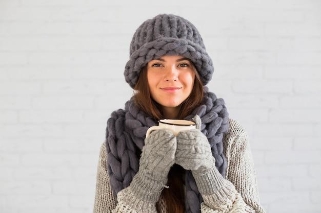 Joyeuse dame en mitaines, bonnet et écharpe avec une tasse dans les mains