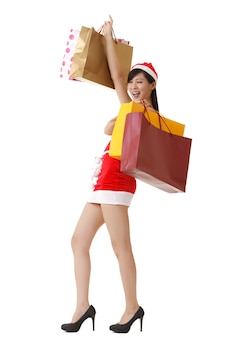 Joyeuse dame de noël tenant des sacs à provisions et souriant, portrait de pleine longueur isolé sur fond blanc.