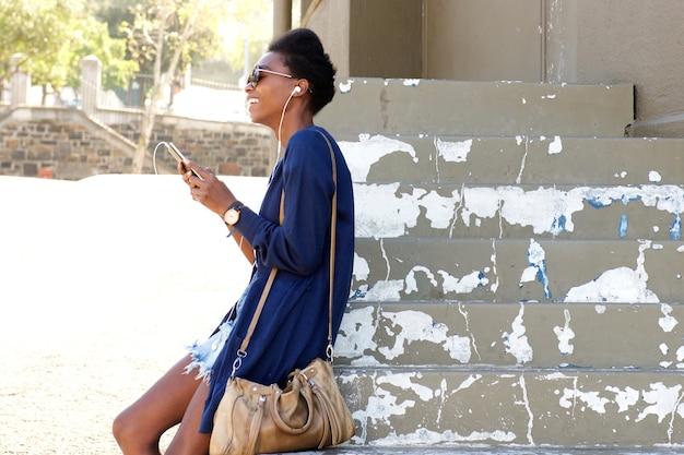 Joyeuse dame noire assis à l'extérieur sur les marches avec un téléphone mobile