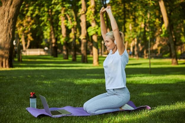Joyeuse dame sportive faisant de l'exercice et souriante assise sur un tapis de yoga devant un ordinateur portable