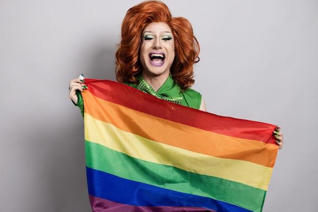 Joyeuse drag queen tenant un drapeau arc-en-ciel - concept lgbtq - focus on face