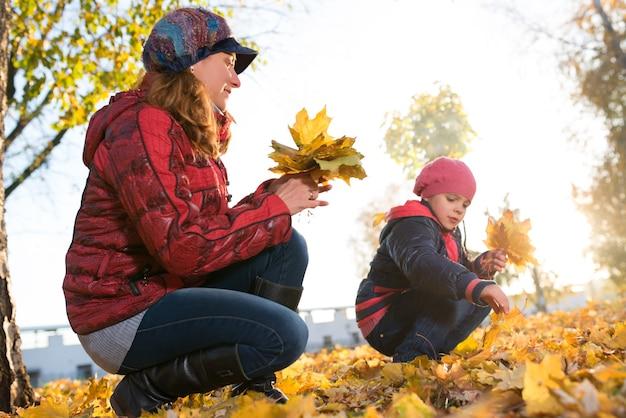 Joyeuse et drôle mère joue avec sa fille positive feuilles d'érable jaune