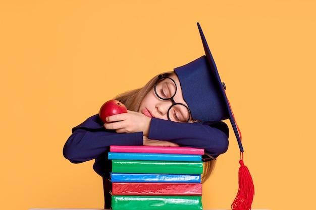 Joyeuse écolière en tenue de graduation glissant tout en tenant une pomme sur une pile de manuels scolaires