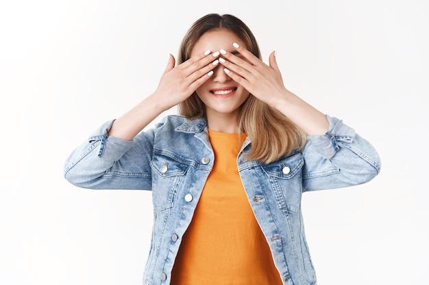 Joyeuse et enthousiaste jolie fille blonde asiatique couvrir la vue souriante anticipant impatiente de voir quel cadeau surprise a préparé des amis b-day party célébration debout mur blanc