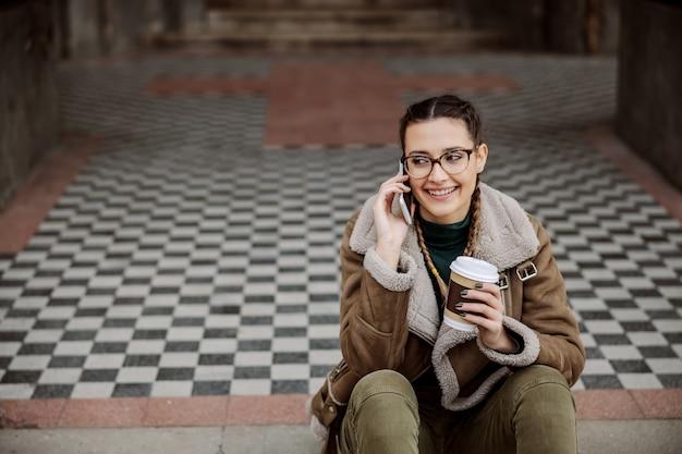 Joyeuse étudiante assise à l'entrée du bâtiment de l'université, ayant une conversation téléphonique et tenant une tasse jetable avec du café.