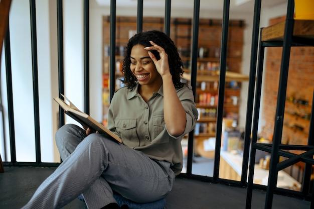 Joyeuse étudiante lit un livre sur le sol dans le café de la bibliothèque
