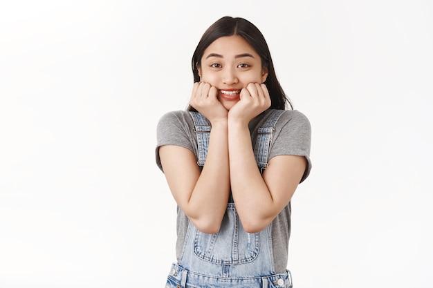 Joyeuse excitée mignonne heureuse fille brune asiatique touche les joues souriante amusée en attendant que le chanteur préféré entre sur scène debout avec joie ne peut pas attendre impatient de voir la performance mur blanc