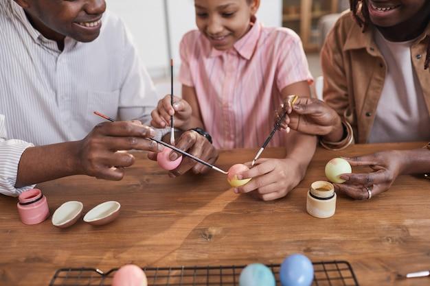Joyeuse famille afro-américaine peignant des œufs de pâques ensemble tout en étant assis à une table en bois et en se liant au projet de bricolage, espace de copie
