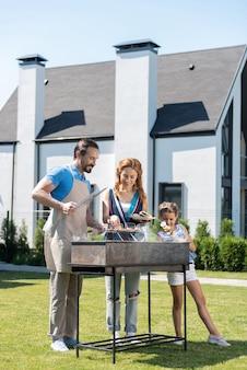 Joyeuse famille agréable debout près du grill tout en profitant de leur week-end