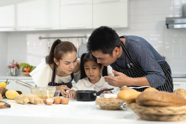 Joyeuse famille asiatique avec sa fille faisant de la pâte préparant des biscuits, sa fille aide un parent à préparer le concept de famille de cuisson