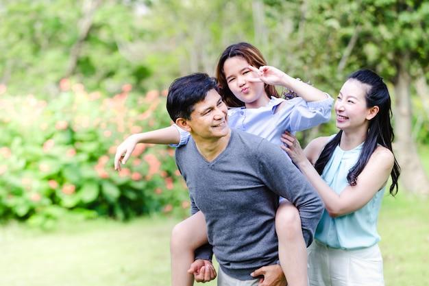 Joyeuse famille ayant pique-nique se détendre ensemble sur la nature verte dans le parc