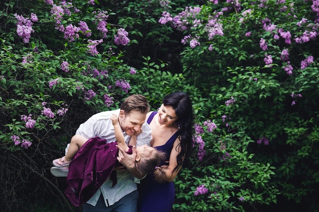 Joyeuse famille heureuse étreignant près des buissons à fleurs lilas.