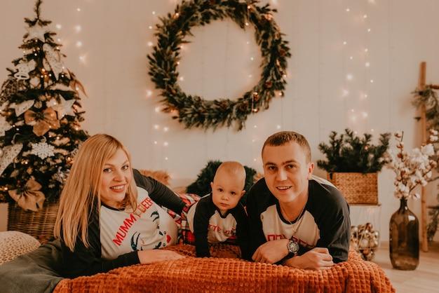 Joyeuse famille heureuse en pyjama avec enfant allongé sur le lit dans la chambre. les vêtements de famille du nouvel an ressemblent à des tenues. cadeaux de célébration de la saint-valentin